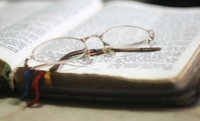 Open Bible with glasses resting on top